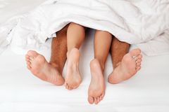 Feet of couple in bed Royalty Free Stock Image