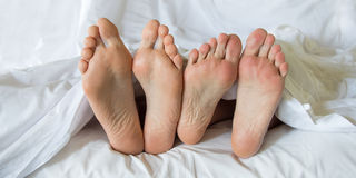 Feet of a couple in a bed Royalty Free Stock Photo
