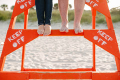 Feet of couple on lifeguard stand keep off Stock Photo