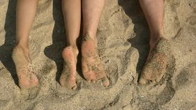 Feet of couple, sand. Legs on sunny beach. Summer trip for two stock footage