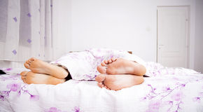 Feet of a couple sleeping side by side Stock Image