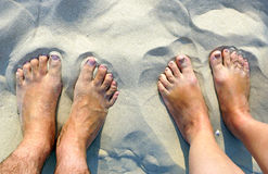 Feet of a couple standing on a white sandy beach Royalty Free Stock Photo