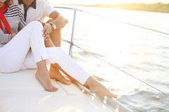 Feet of a couple stting on sailboat deck in the sea Stock Photos