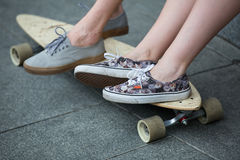 Feet couple of teenagers on the longboard closeup Stock Images