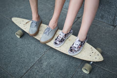 Feet couple of teenagers on the longboard closeup Royalty Free Stock Photos