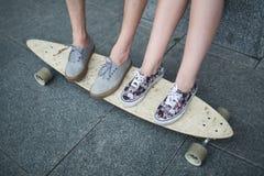 Feet couple of teenagers on the longboard closeup Royalty Free Stock Photos