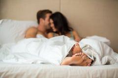 Feet of couple under blanket. Stock Image