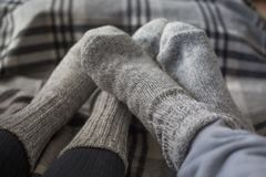 Feet in woollen socks. Feet of couple in woollen socks on checkered blanket, home comfort and love concept Royalty Free Stock Photography