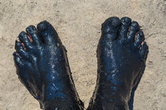 Feet covered with a black therapeutic mud Royalty Free Stock Image