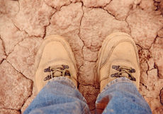 Feet on cracked earth Royalty Free Stock Image