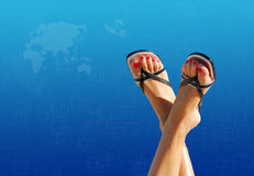 Feet crossed with blue world map in background Royalty Free Stock Photos