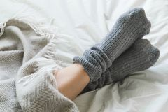 Feet crossed with gray socks on bed under blanket. Pair of feet in gray socks on a bed under a cozy blanket stock image