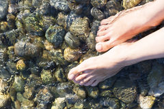 Feet in the crystal clear sea water Stock Photos