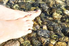 Feet in the crystal clear sea water Stock Images