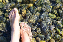 Feet in the crystal clear sea water Stock Photo