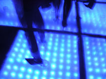 Feet on a dance floor. Feet on a back lit dance floor stock image