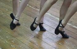 Feet of dancing girls in black dance shoes stock photos