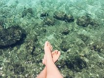 Feet dangling above water. Feet dangling above clear water with rocky floor below royalty free stock photos