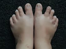 Photo of feet on a black door mat royalty free stock photography