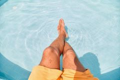 Feet dipped in swimming pool water stock images