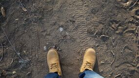 Feet on dirt ground