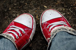 Feet in dirty red sneakers and jeans outdoors. Stock Photos