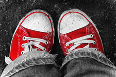 Feet in dirty red sneakers and jeans outdoors. Royalty Free Stock Photos