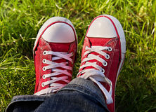 Feet in dirty red sneakers outdoors. Stock Images