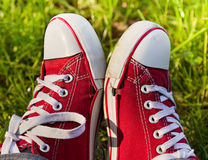Feet in dirty red sneakers outdoors. Royalty Free Stock Photo