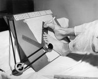 Feet of a disabled man using a drafting board. (All persons depicted are no longer living and no estate exists. Supplier grants that there will be no model Stock Photos