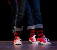 Feet of a  duo of hip-hop performers. In jeans and red sneakers Royalty Free Stock Images