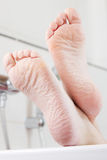 Feet on the edge of a bathtub Royalty Free Stock Image