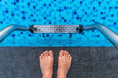 Feet on the edge of the blue swimming pool Stock Photos