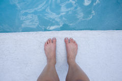 Feet at the edge of the pool Stock Photography