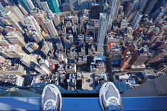 Feet on the edge of tall building. Jumpers feet on the edge of a very tall building thinking of committing suicide, depression, stress concept. Empire State stock photos
