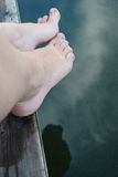 Feet by edge of water. Closeup of pair of feet dangling over water royalty free stock photography