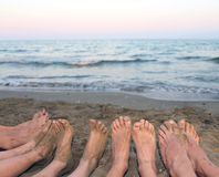 Feet of a family barefoot by the sea on the beach in summer Royalty Free Stock Photos