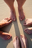 Feet of a family in the fine sand of the beach Royalty Free Stock Images