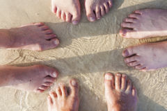 Feet of a family in the fine sand Stock Photos