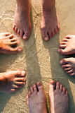 Feet of a family in the fine sand of the beach Royalty Free Stock Photography