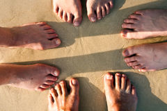 Feet of a family in the fine sand of the beach Stock Images