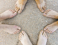 Feet of a family of four at the beach Stock Photography