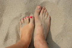 Feet of father and his teen daughter on the sand Stock Images