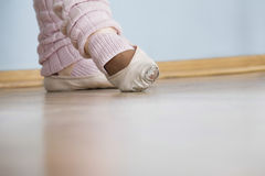 Feet Of Female Ballerina. Low section of feet of female ballerina in rehearsal room royalty free stock image