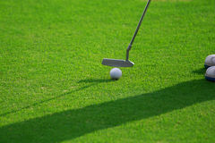 Feet of female golf player putting at green. Royalty Free Stock Photography