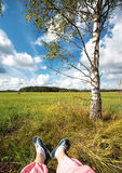 Feet at field with beautiful clouds Royalty Free Stock Photography