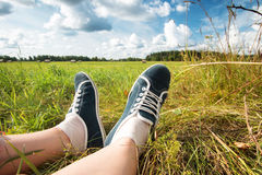Feet at field with beautiful clouds Royalty Free Stock Photo