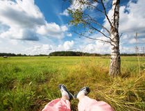 Feet at field with beautiful clouds Stock Photography