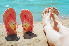 Feet and flip-flops on beach. Flip-flops and foot against ocean blue water royalty free stock photo