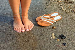 Feet and flip flops on the beach Royalty Free Stock Image